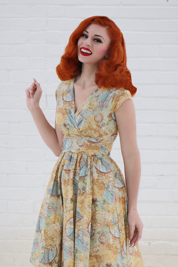 Smiling model with red hair wearing a vintage style yellow and blue dress.