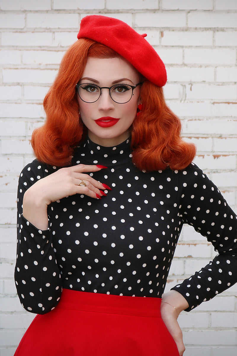 Model wearing a black top with white polka dots, red beret and red skirt.