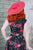 Back-shot of model wearing red sun-hat and a black retro dress with rose pattern.