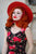 Waist-up shot of model wearing red hat and retro dress.