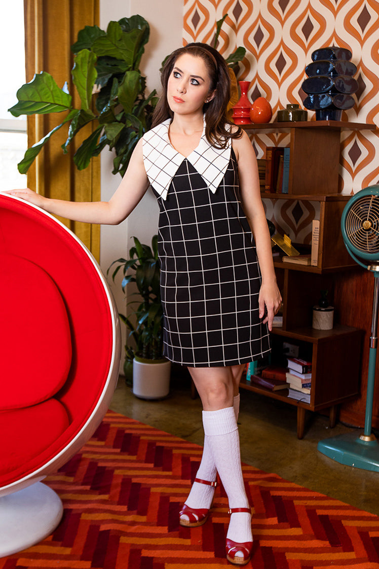 Model wearing a retro era styled dress standing in a vintage room