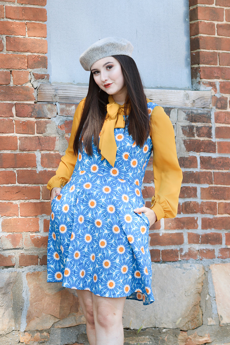 Model wearing blue and mustard yellow top standing in front of brick building.