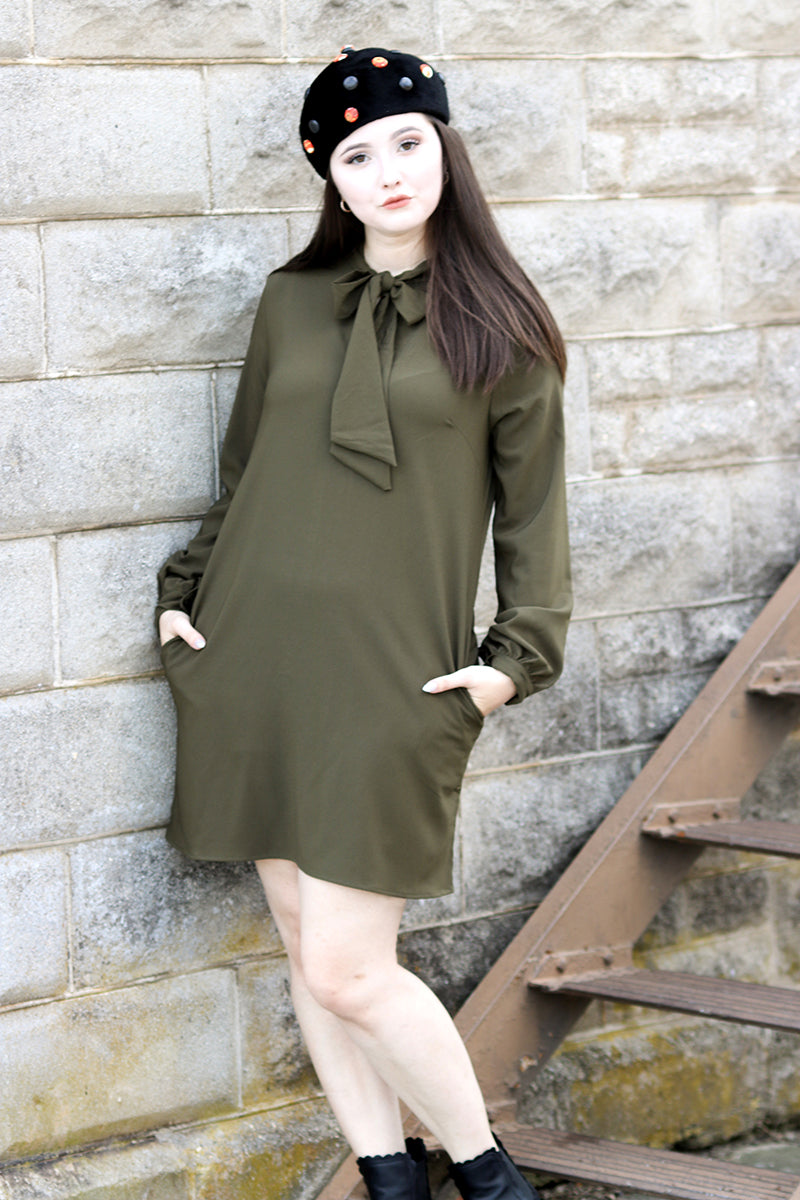Model wearing olive green frock standing in front of white brick building.