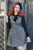 Ginger haired model leaning against an outdoor archway wearing a black beret and steampunk style dress.