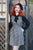 Model with red hair standing outside wearing a retro dress and black beret.