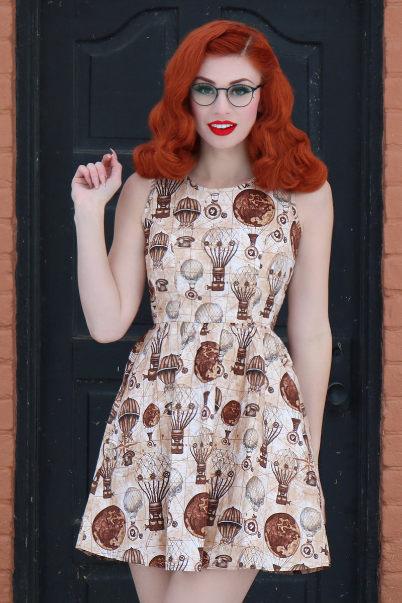 Model wearing vintage style dress in front of door.