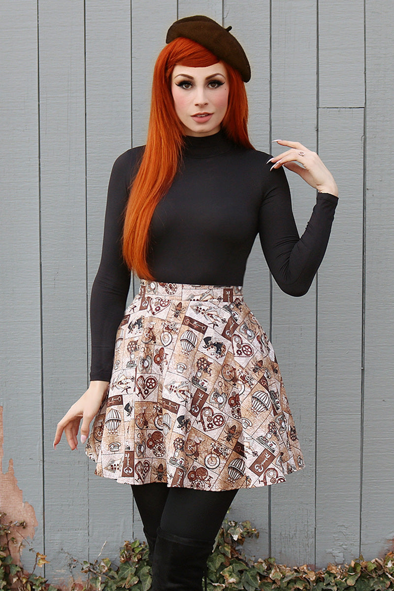 Model with red hair wearing a black long sleeve top, black beret and steampunk style skirt.