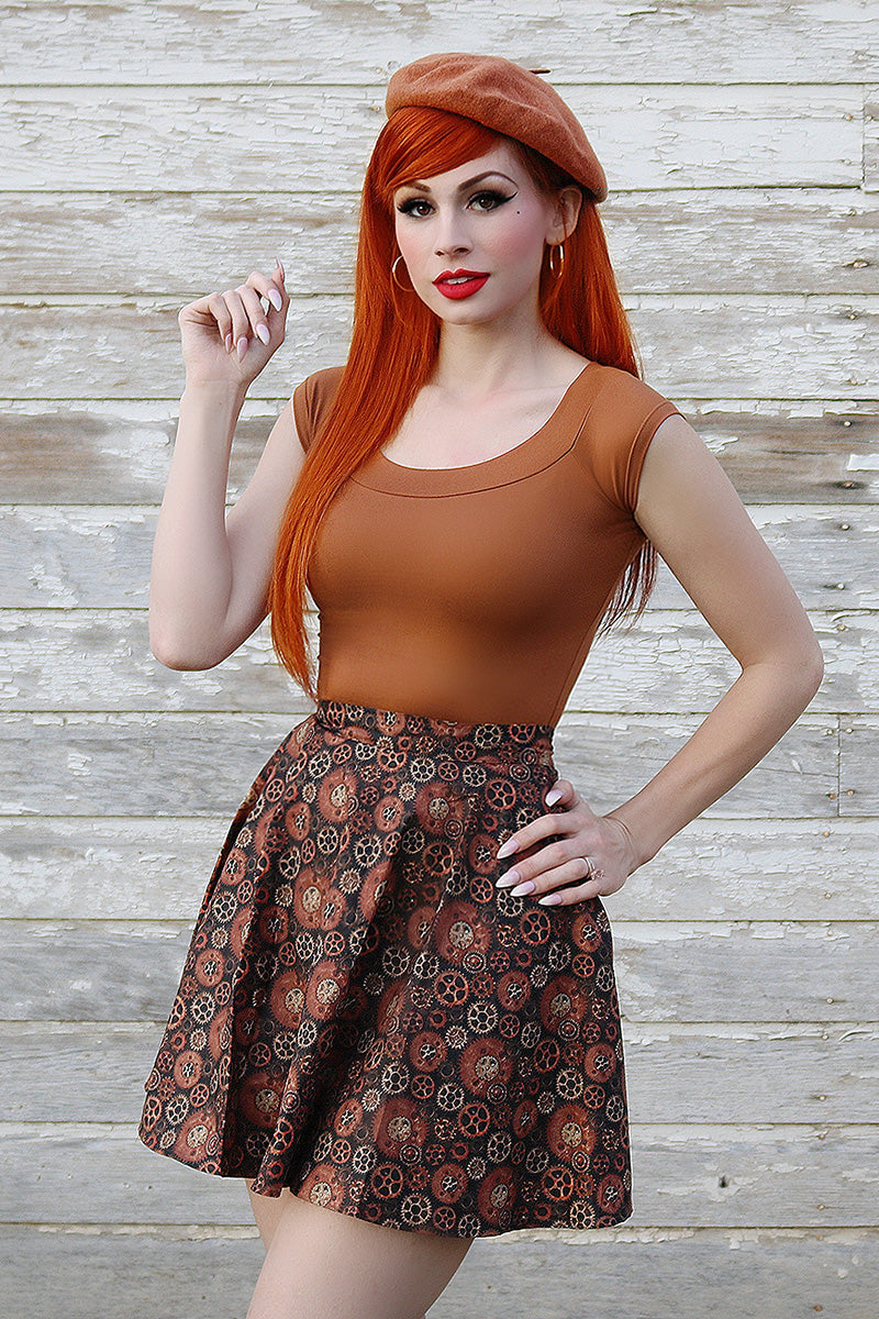 Model with red hair wearing a skater skirt and brown top.