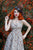 Front shot of model with red hair standing against greenery in a steampunk tophat and retro dress.