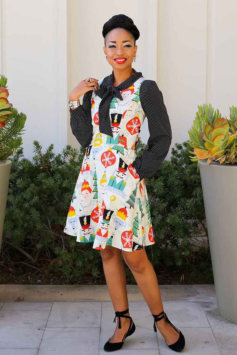 Model wearing a holiday inspired nutcracker print dress
