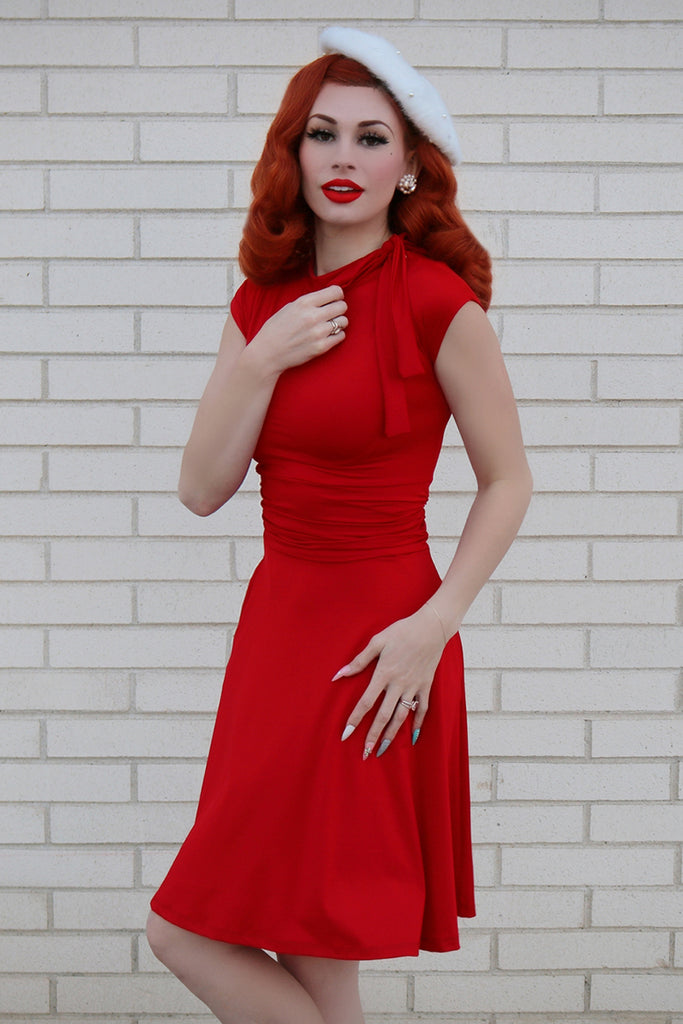 Model wearing red vintage dress and white beret.