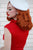 Backshot of model wearing a sleeveless red dress and white beret.
