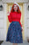 Model smiling and looking off-camera wearing a red mock turtleneck, white beret and blue retro skirt.