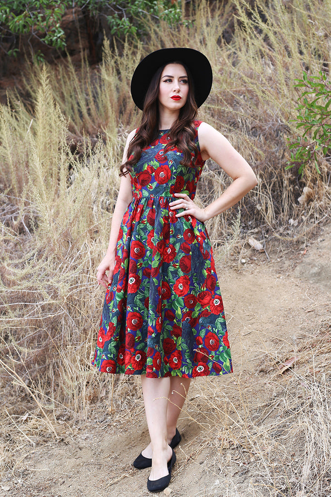 Brunette model standing on a hillside, wearing a retro inspired dress.