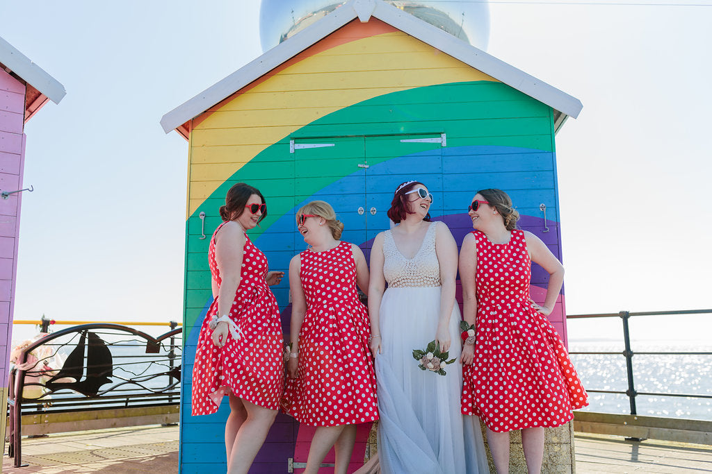 Bride and Bridesmaid in front of a rainbow beach hut