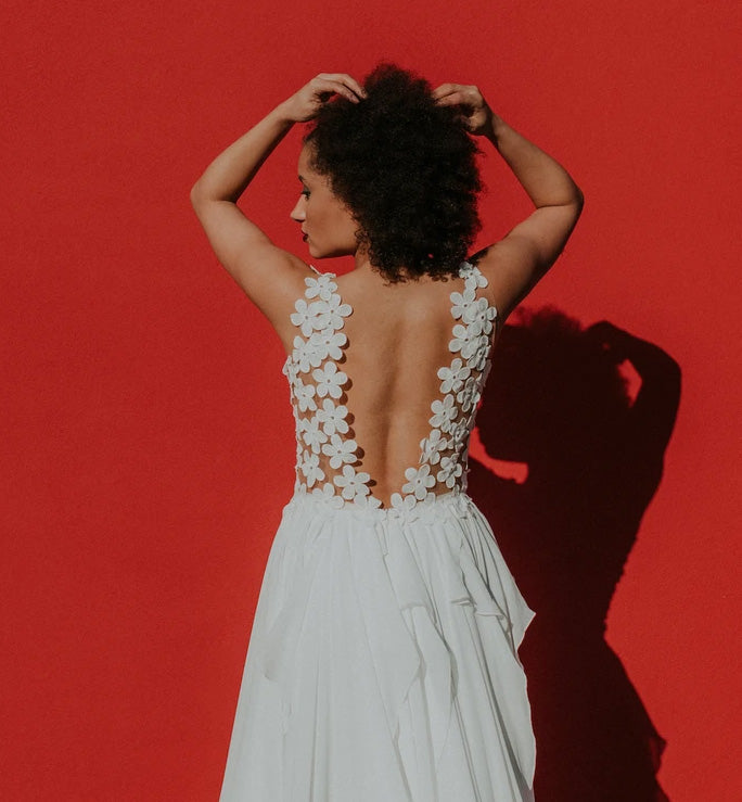 Floral backless wedding dress against a red backdrop