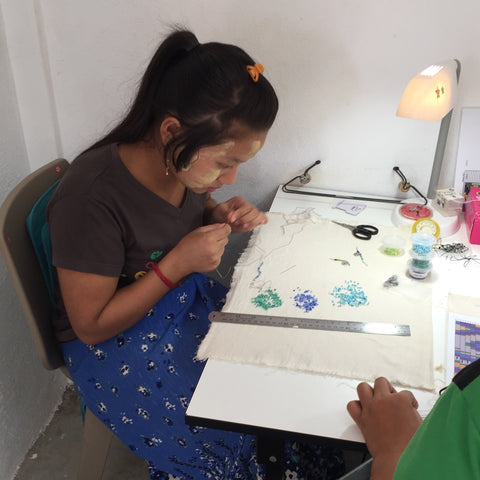 young woman from Myanmar making jewelry at factory in Thailand