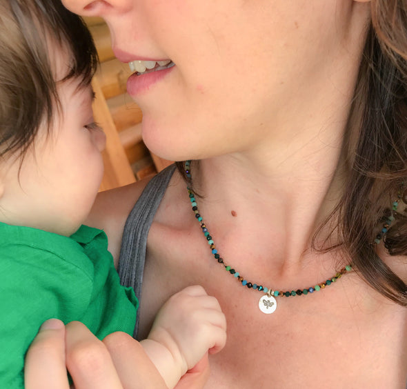 Baby Ellie and Mother Morgan wearing handmade green and brown color mix crystal necklace with dragonfly silver pendant designed by Elly Bashara in Bozeman, MT