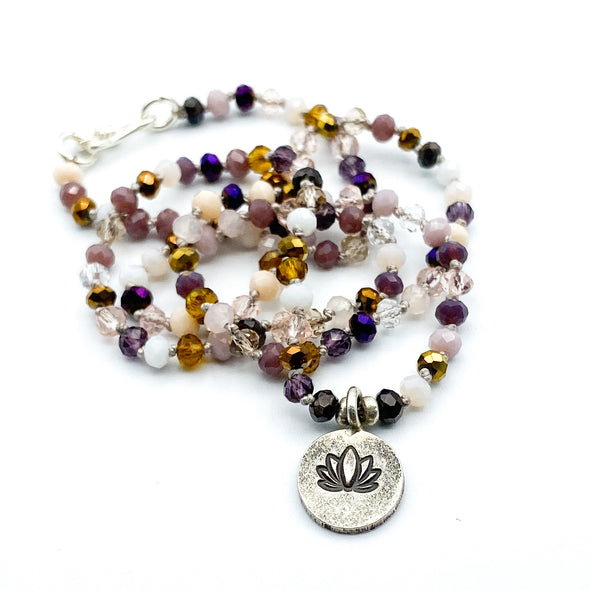 Elly Bashara designer from Bozeman, Montana handmade lotus flower pendant crystal necklace silver charm and clasp hand knotted on gray silk cord in shades of plum purple gold pink color mix