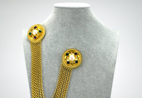 This duette-style brooch can either be worn to one side or as a fastener for a cardigan or cape. It features faux gemstones in green and purple and each brooch is centered with a pearl. Ben Amun is the trade name of Isaac Manevitz, who for decades has collaborated with celebrities such as Lady Gaga in creating custom costume pieces.