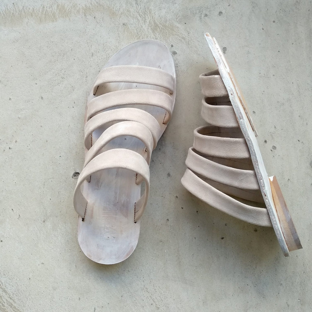White strappy leather slides. 62