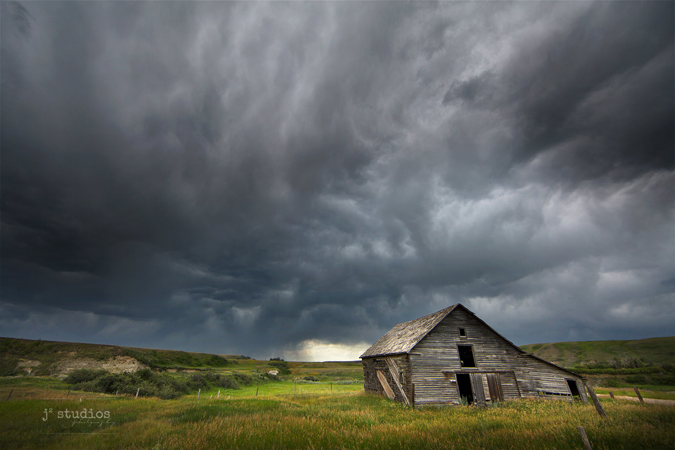 Dramatic image of the badlands in Sharples featuring a weathered barn standing steadfast against the incoming storm.  Storm photography of Alberta.