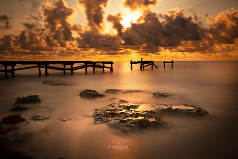 Image of the silky waters of the Caribbean Sea at sunrise in Playa del Carmen. Weathered and battered wooden pier frames this beautiful  photograph.