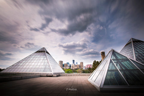 Moody image of trailing clouds over Muttart Conservatory. Three iconic glass pyramids framing the Edmonton City Skyline.