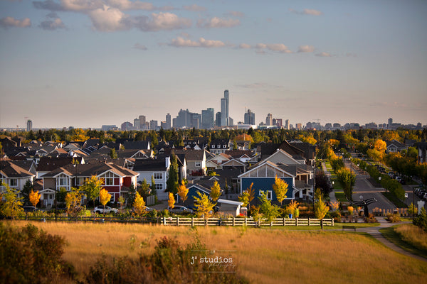 Image of Edmonton Skyline from Griesbach Hill in Autumn. This picture has a San Francisco vibe featuring colorful houses against metropolitan skyline.  Postcard image of YEG by Larry Jang.