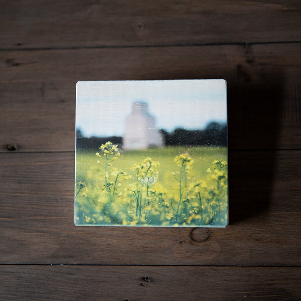 Photo Block featuring Canola Flowers in a field with a grain elevator in background. Handmade in Edmonton, Alberta, Canada by Larry & Christina Jang of J² Studios Photography & Craft. Unique decor ideas for rustic modern homes or farmhouse.