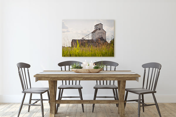 Grain elevator canvas print hanging on wall of rustic dining room.