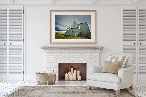 Framed print of Fort Macleod grain elevator on display above fireplace mantle in a living room of modern home.  Wall decor ideas. for cozy rooms