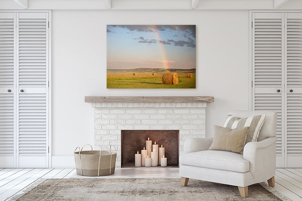 Prairie themed canvas print of hay bales & rainbow colors in living room with a fireplace.