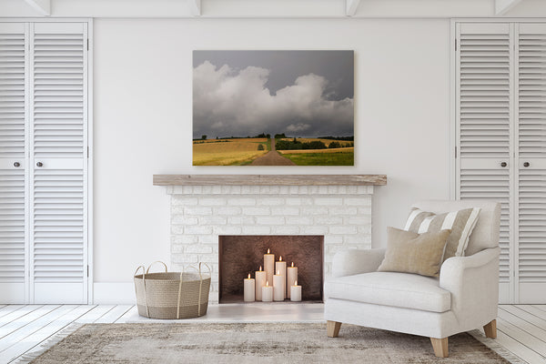 Living room decor with a fireplace. Big print of a prairie country road leading into summer rain storm.