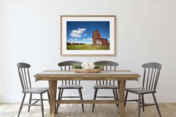 Framed art print of train passing a grain elevator hanging on a dining room wall.
