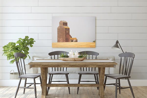 Canvas print of harvested wheat field hanging in rustic modern dining room.