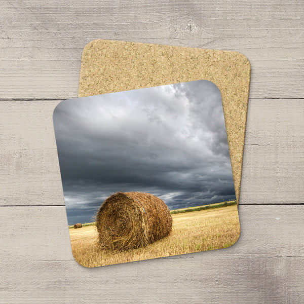 Coasters set of a Hay Bale sitting in farmers field awaiting an incoming storm in Pincher Creek, Alberta by Larry Jang.