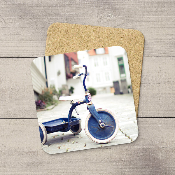 Coasters of a Blue Tricycle parked on the cobblestone streets of Bergen, Norway by Larry Jang.