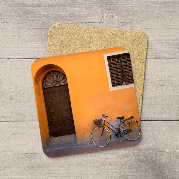 Cork coasters with a photo of bicycle parked against an orange wall in Piza, Italy by Larry Jang.
