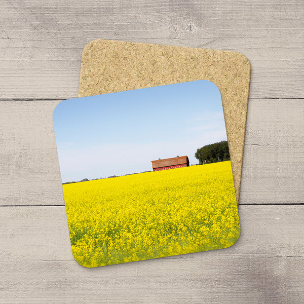 Photo coasters of a red barn sitting in a field of canola. Home accessories by Edmonton based photographer & artist, Larry Jang