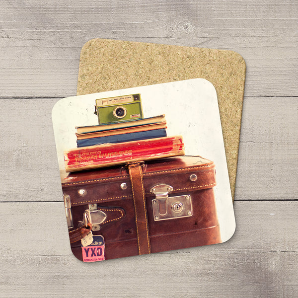Home Accessories. Photo Coasters of Kodak Camera sitting on top of vintage books & suitcase. Municipal Airport Luggage Tag YXD.  Modern functional art by Edmonton artist & photographer Larry Jang.