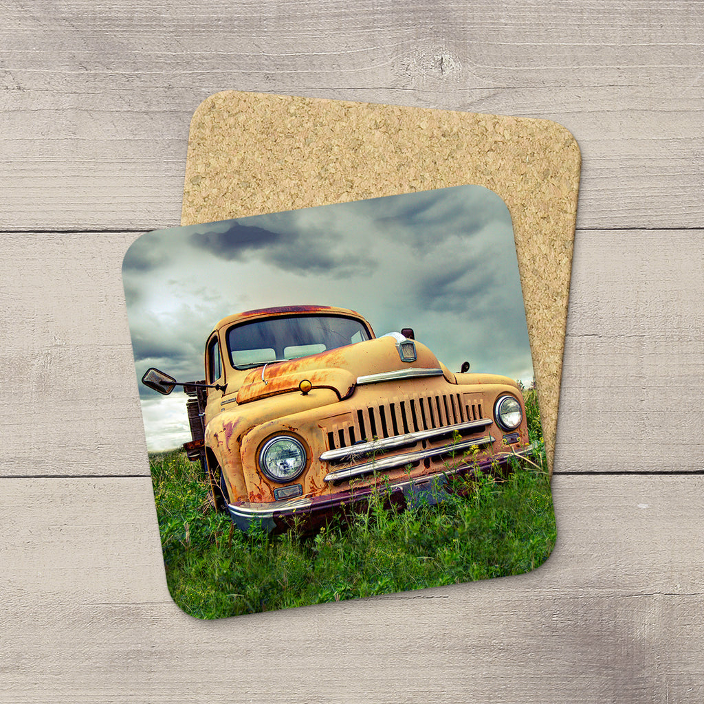 Photo coaster of a rusty International truck sittiing in a field by acclaimed Canadian Photographer Larry Jang.