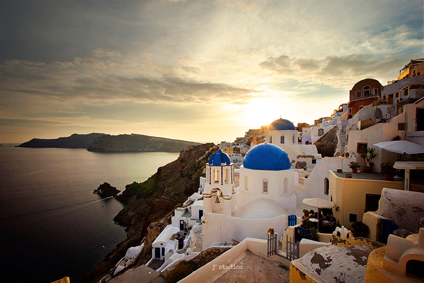 Photograph of the Village of Oia in Island of Santorini, Greece at sunset featuring Saint Spyridon Church And Anastasis Church famous blue domed churches. Travels as excellent art prints by Larry Jang and J2 Studios Photography.