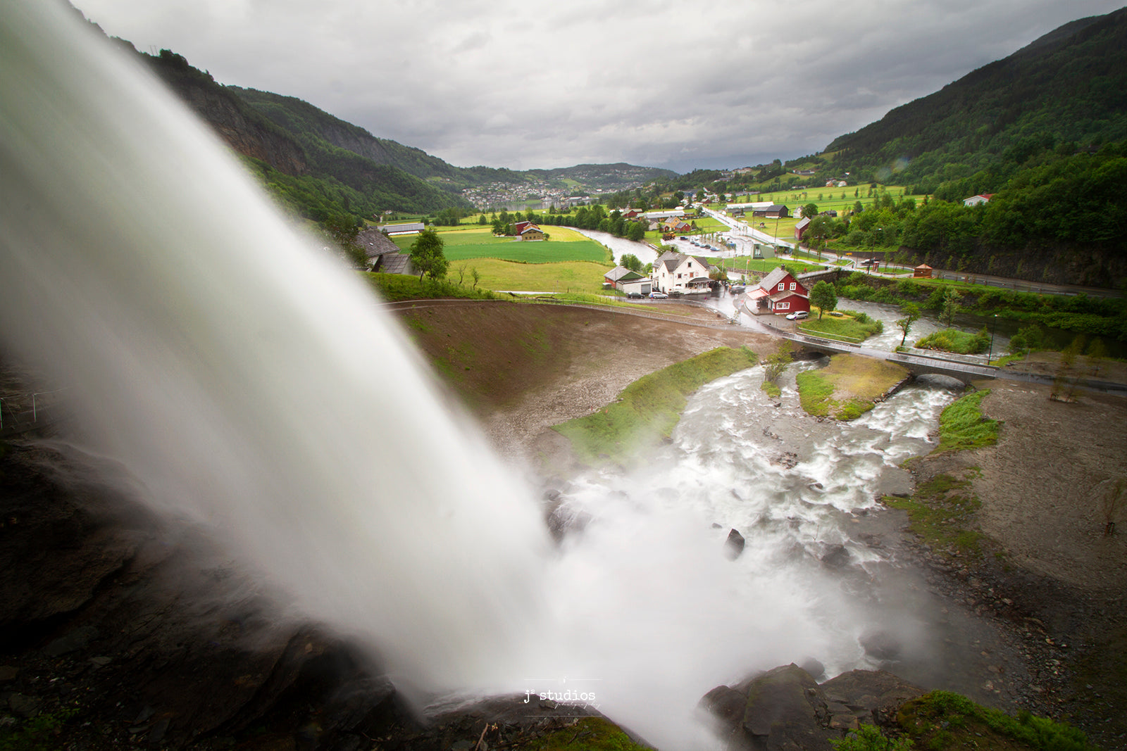 Beautiful picture of water flowing from Steinsdalfossen into the green valley below. Colorful houses in Norway are also featured here. Stunning Landscape Photography by Larry Jang