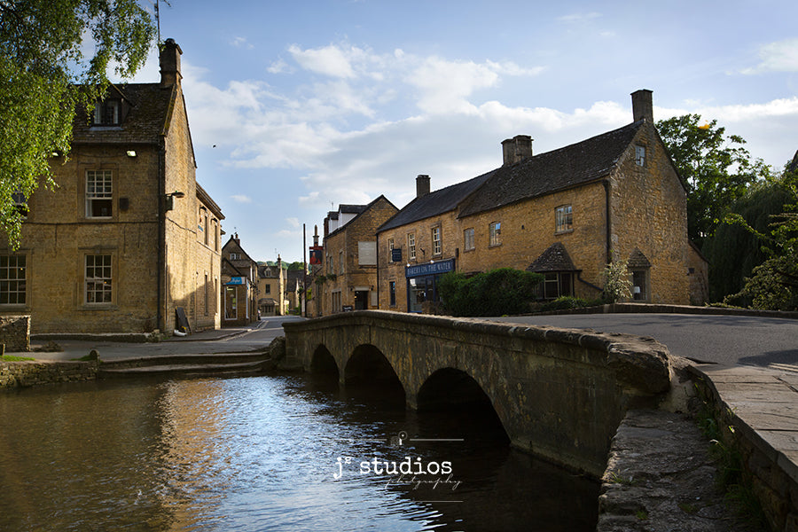 Charming image of the famous village in Cotswold's with River Windrush flowing underneath arched stone bridge.
