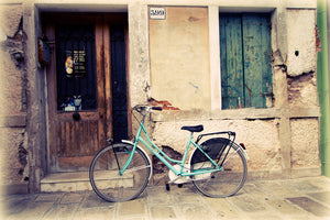 Aquamarine Bicycle is an art print of a bike parked in Burano, Italy.