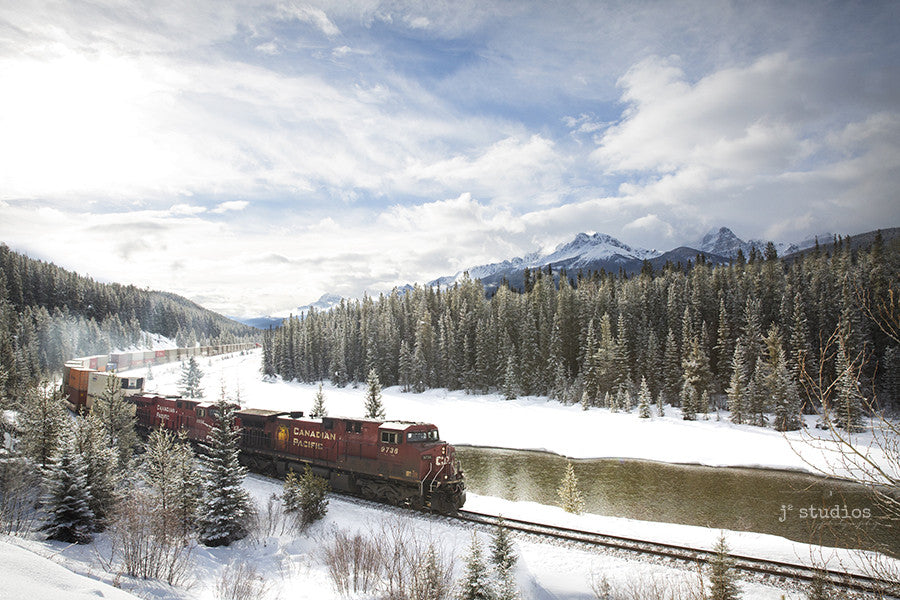 Around the Bend is an art print of a CP Rail Cargo train roaring through the snow capped peaks of Bannf National Park. Alberta Rocky Mountain Photography.
