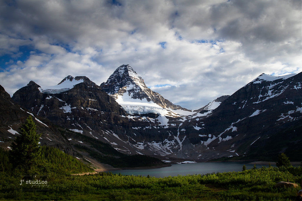 Beautiful stunning moody dramatic art print of Mount Assiniboine in Canadian Rockies towering over Lake Magog under layers of clouds. Matterhorn photography by Larry Jang.