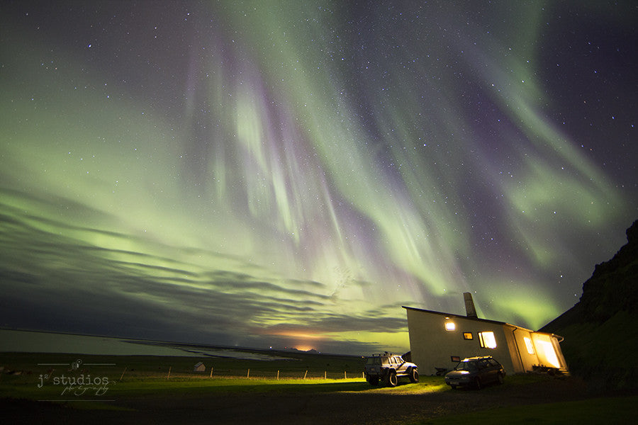 Aurora Rain is an image of the Northern Lights dancing over a house and ocean in Southern Iceland. Aurora photography.