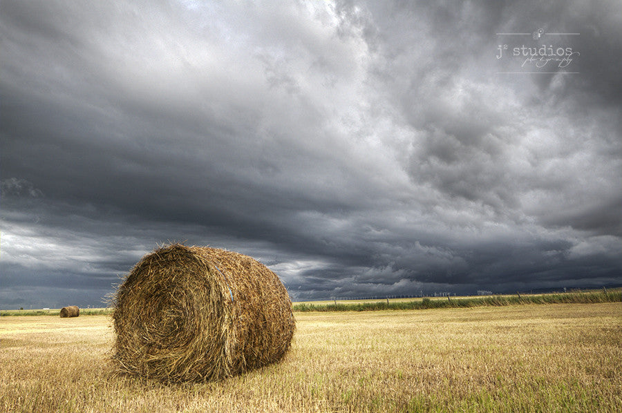 Bale Under the Storm is an art print of a farmers field that remains calm despite the incoming storm. Alberta photography.